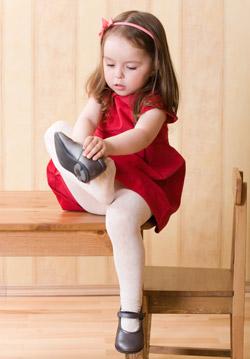 Маленькая модница одевает башмачки